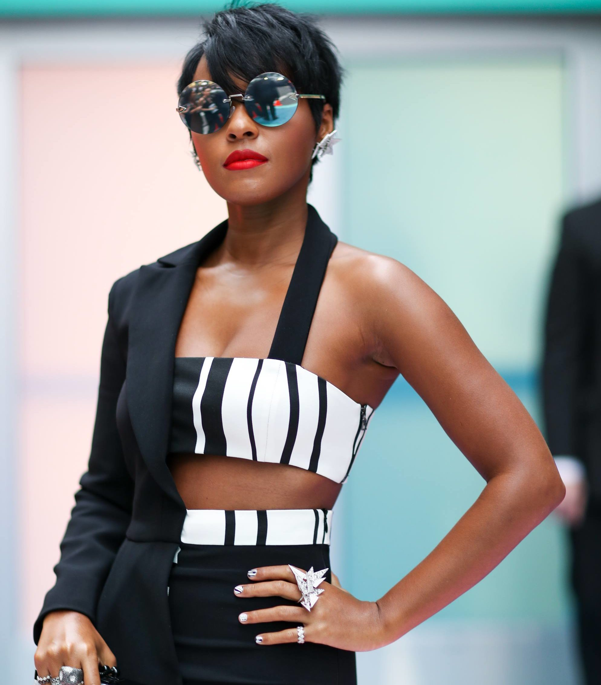black pixie hairstyles: close up shot of janelle monae with black pixie haircut, wearing sunglasses, a red lipstick and a designer suit and top
