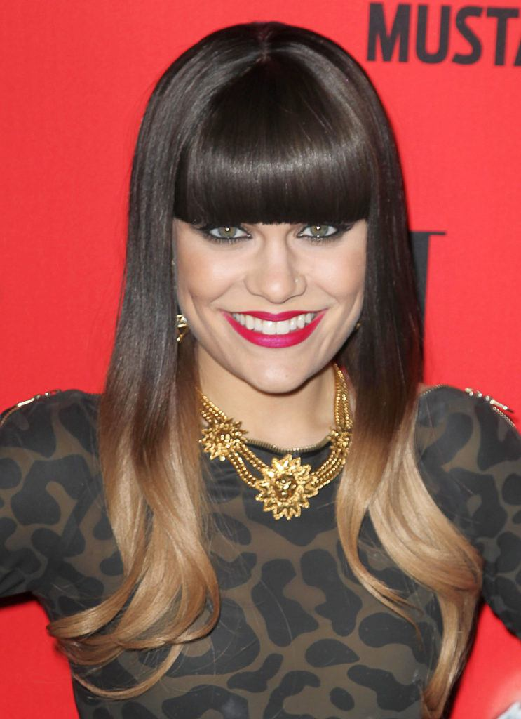 close up shot of jessie j with black ombre that ends with blonde tips, wearing leopard dress and posing on red carpet