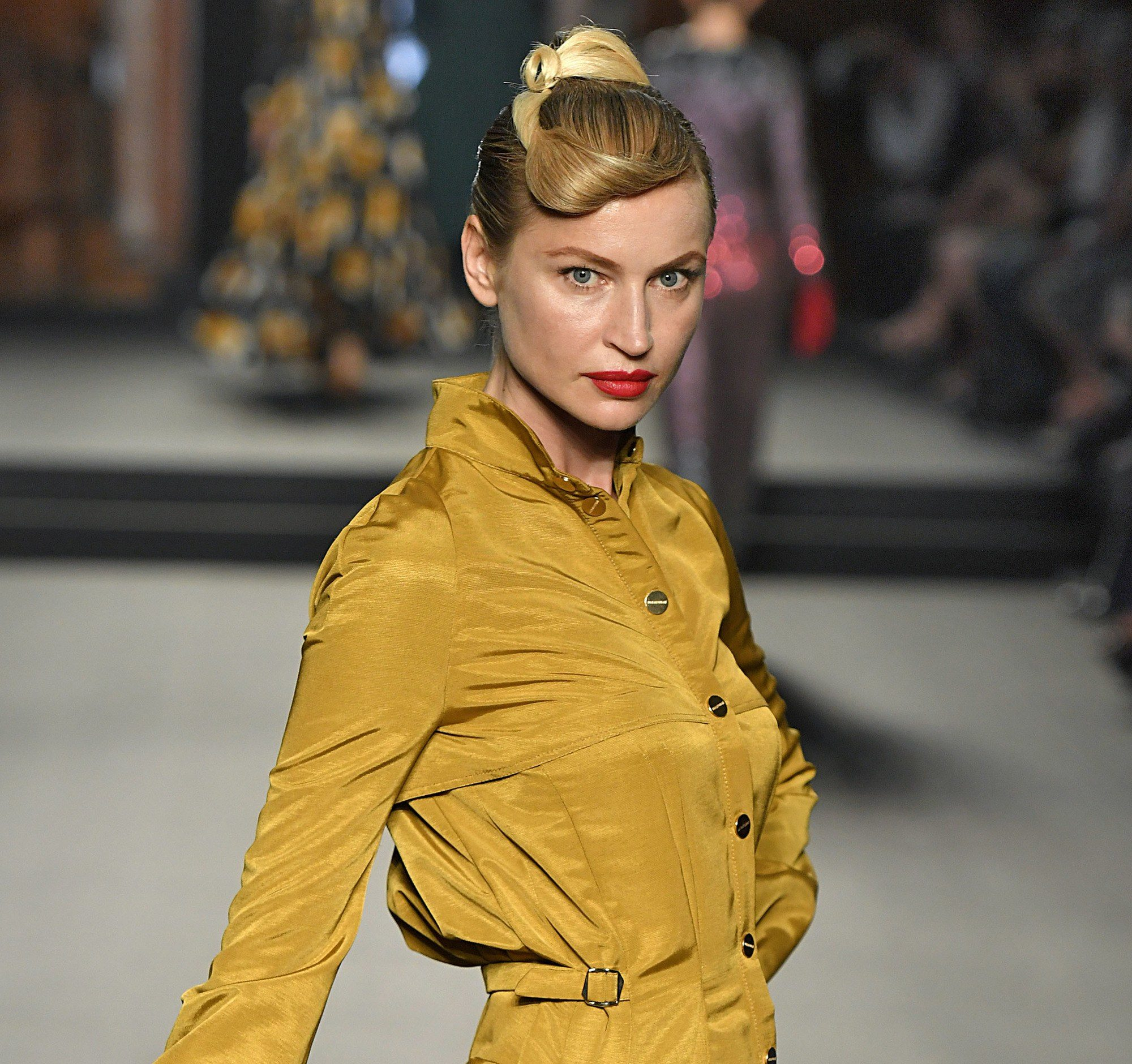Paris Haute Couture Week fw18: close up shot of a woman on the runway with golden blonde hair styled into a retro twist updo, wearing mustard dress and posing