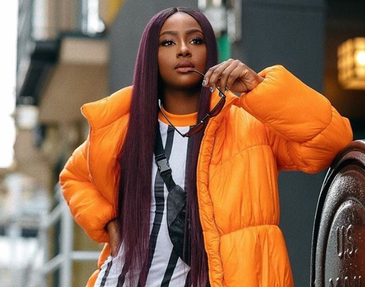 best hair colour for black women: close up shot of black woman with long purple hair, wearing orange jacket and stripped white shirt