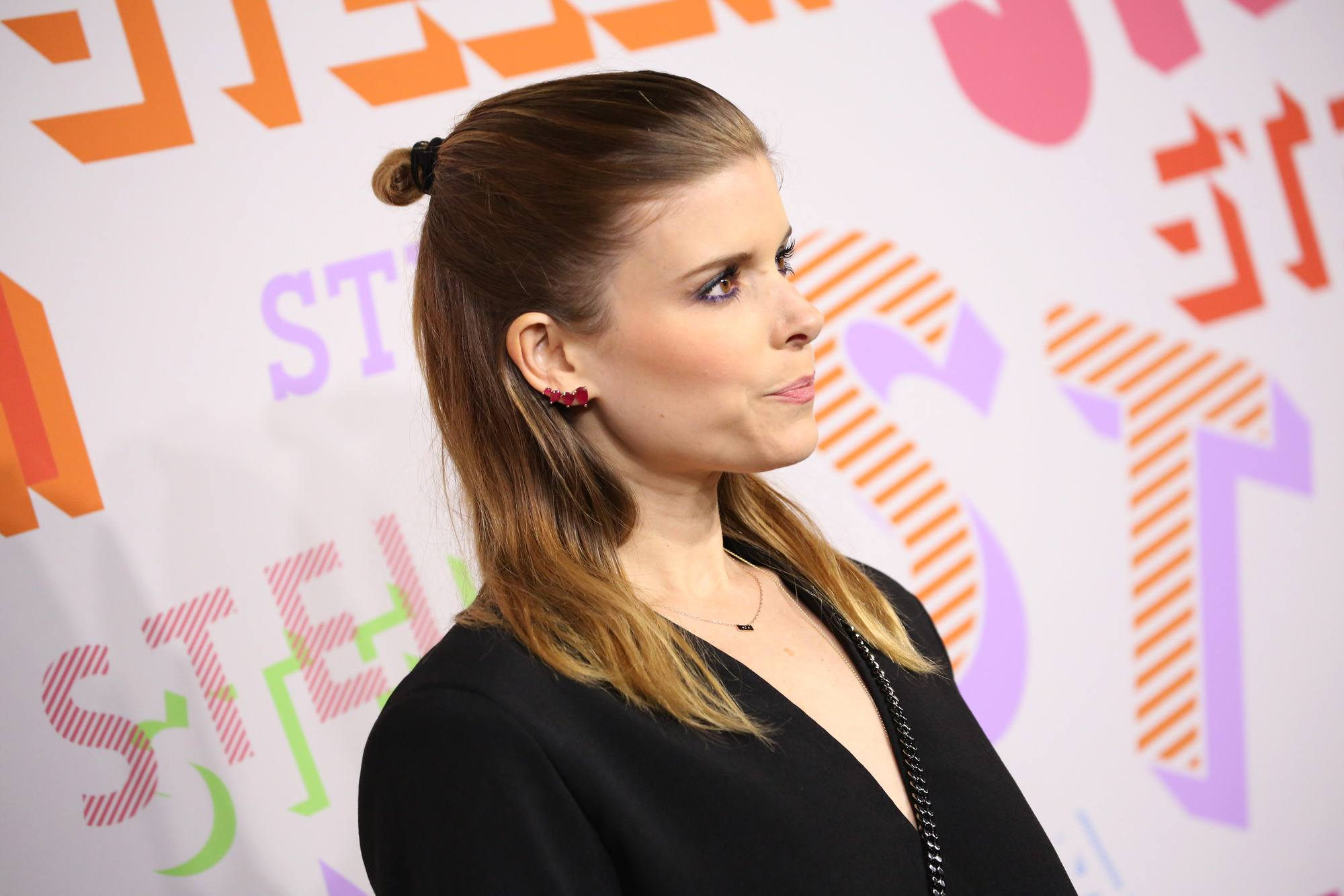 actress kate mara with shoulder length brunette hair in a half up topknot style