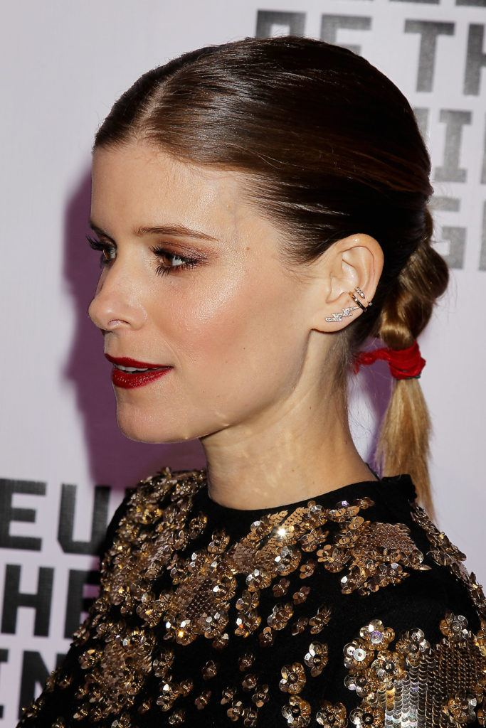close up shot of kate mara with low twisted ponytail hairstyle, wearing all black on the red carpet
