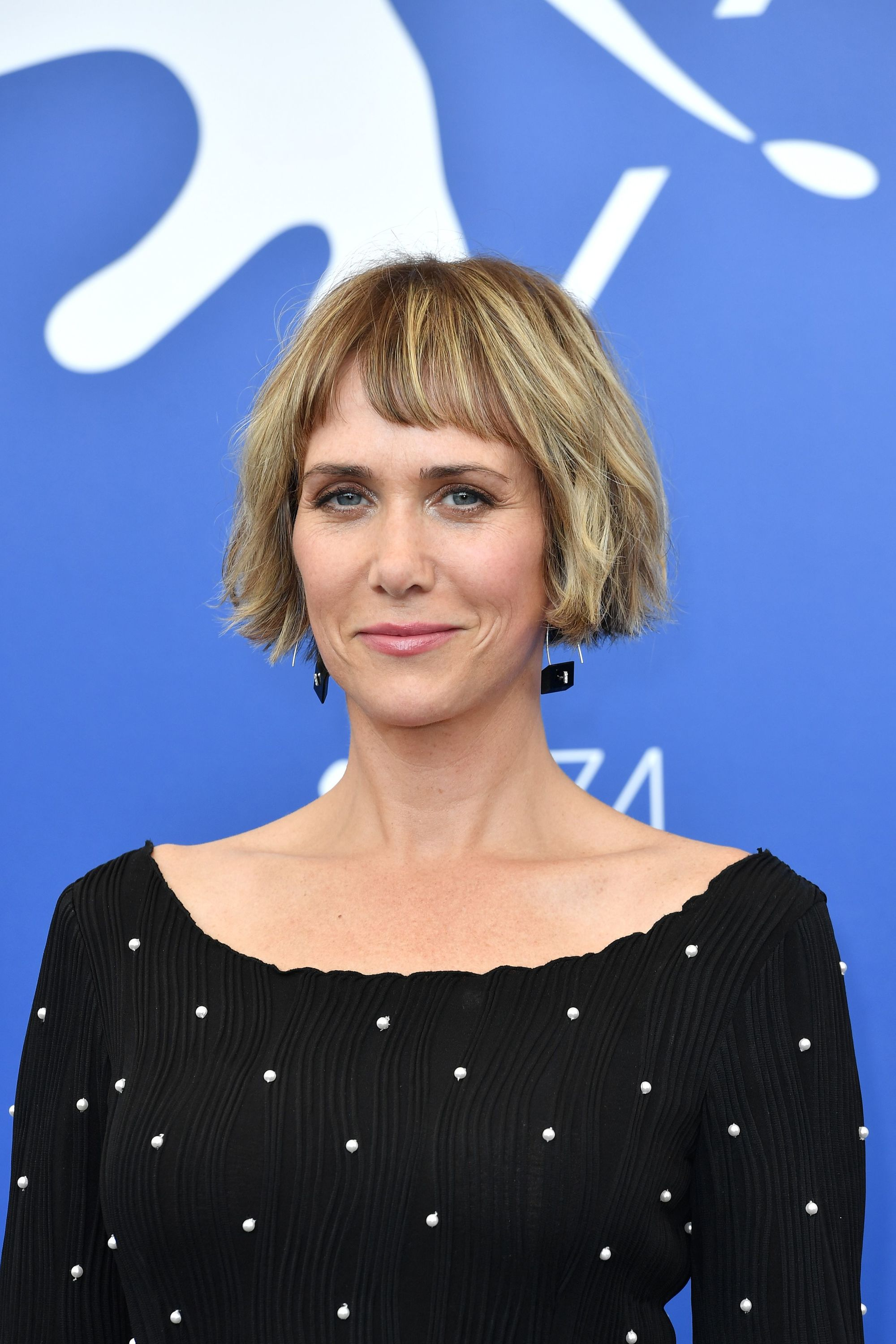 close up shot of kirsten wig with short bob haircut with sunny highlights in it, wearing black top with pearls on it and statement earrings