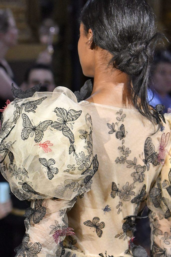Paris Haute Couture Week fw18: close up shot of a model with dark brown hair styled into a low knotted bun, wearing a floral dress with puffy sleeves on the Schiaparelli runway