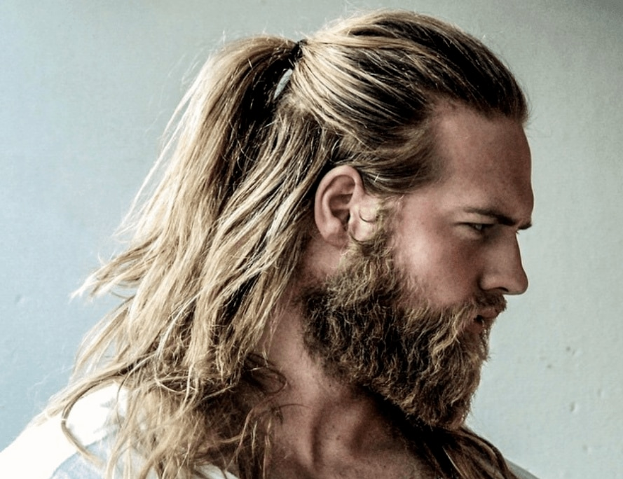 Viking hairstyles: Man with long dark blonde hair styled into half up ponytail with rugged beard, wearing white shirt