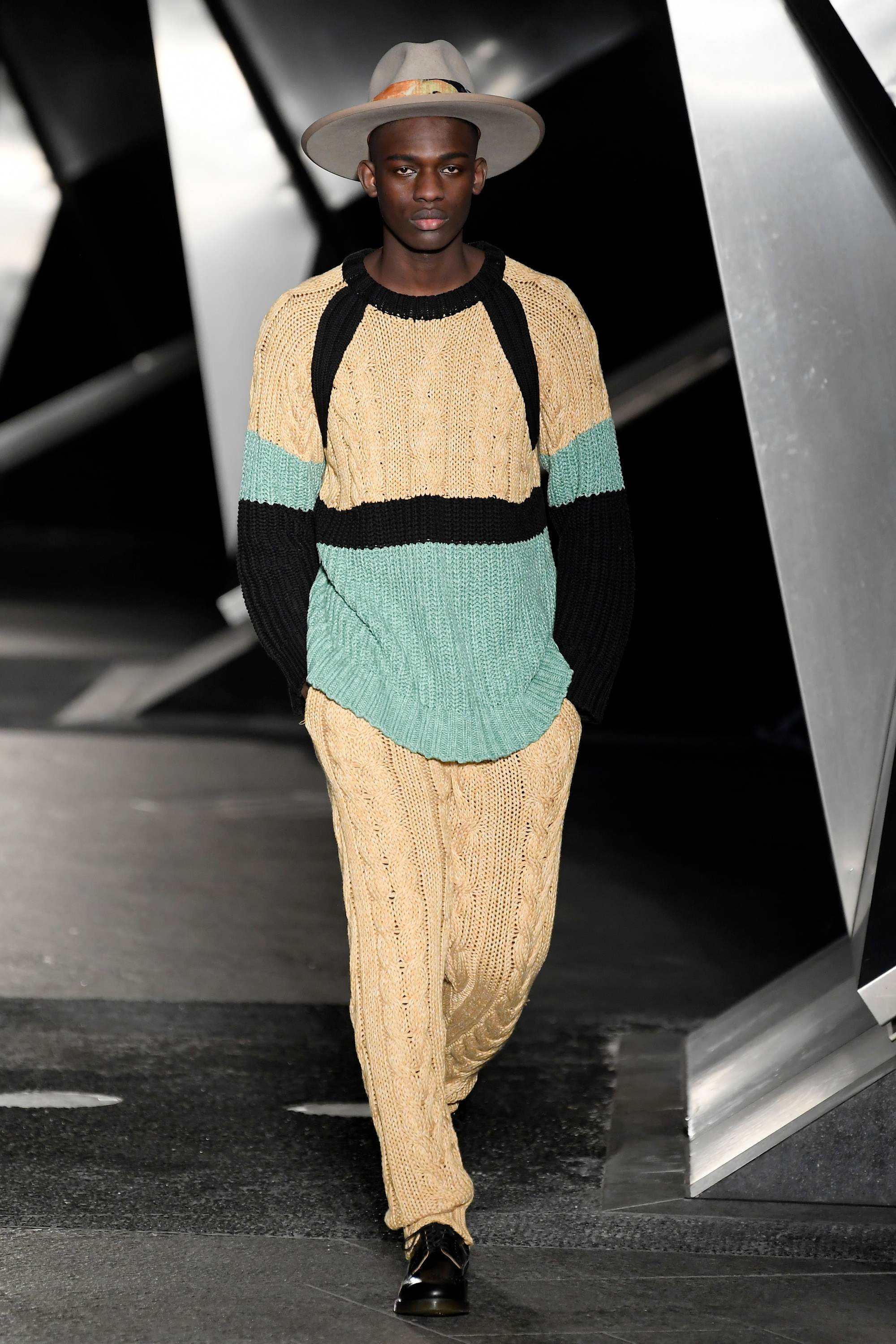London Fashion Week Men's: Model on runway with fedora hat and yellow outfit.