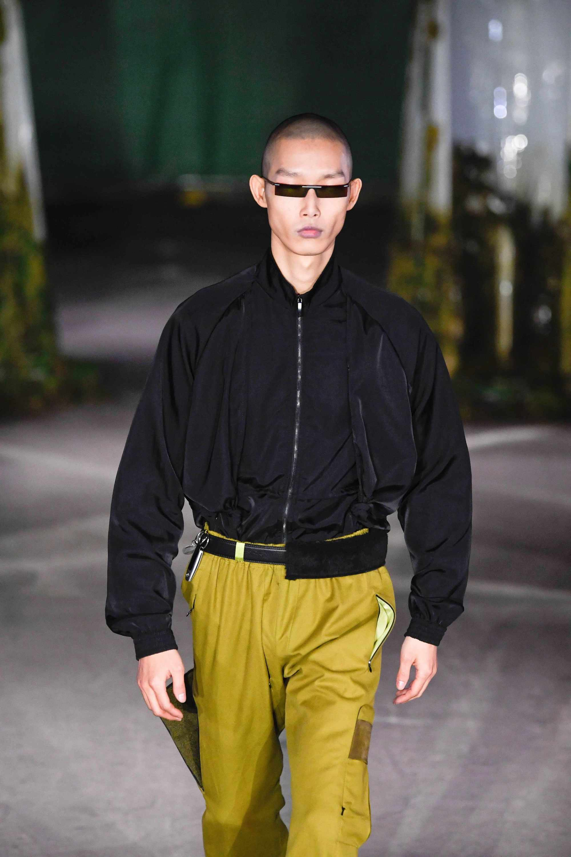 London Fashion Week Men's: Model on Cottweiler runway with shaved hair wearing micro black sunglasses.