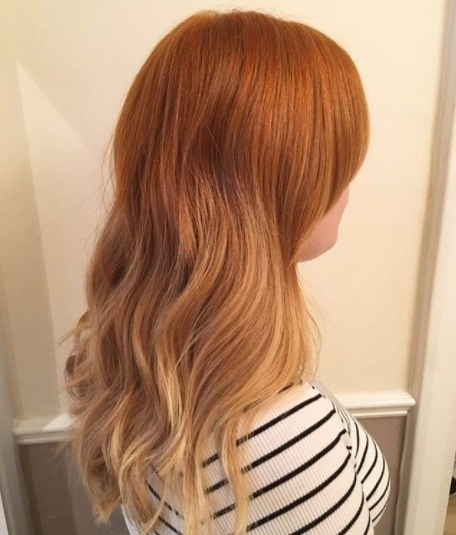 side view of a woman with light copper ombre wavy hair