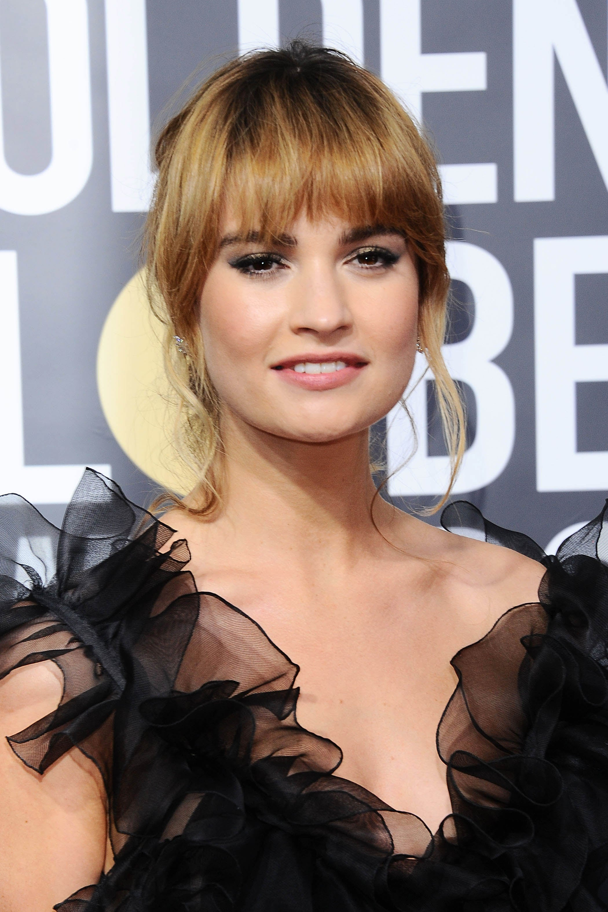 lily james with a full fringe and updo hairstyle