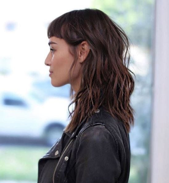 side view of woman with brown medium length wavy hair and micro fringe