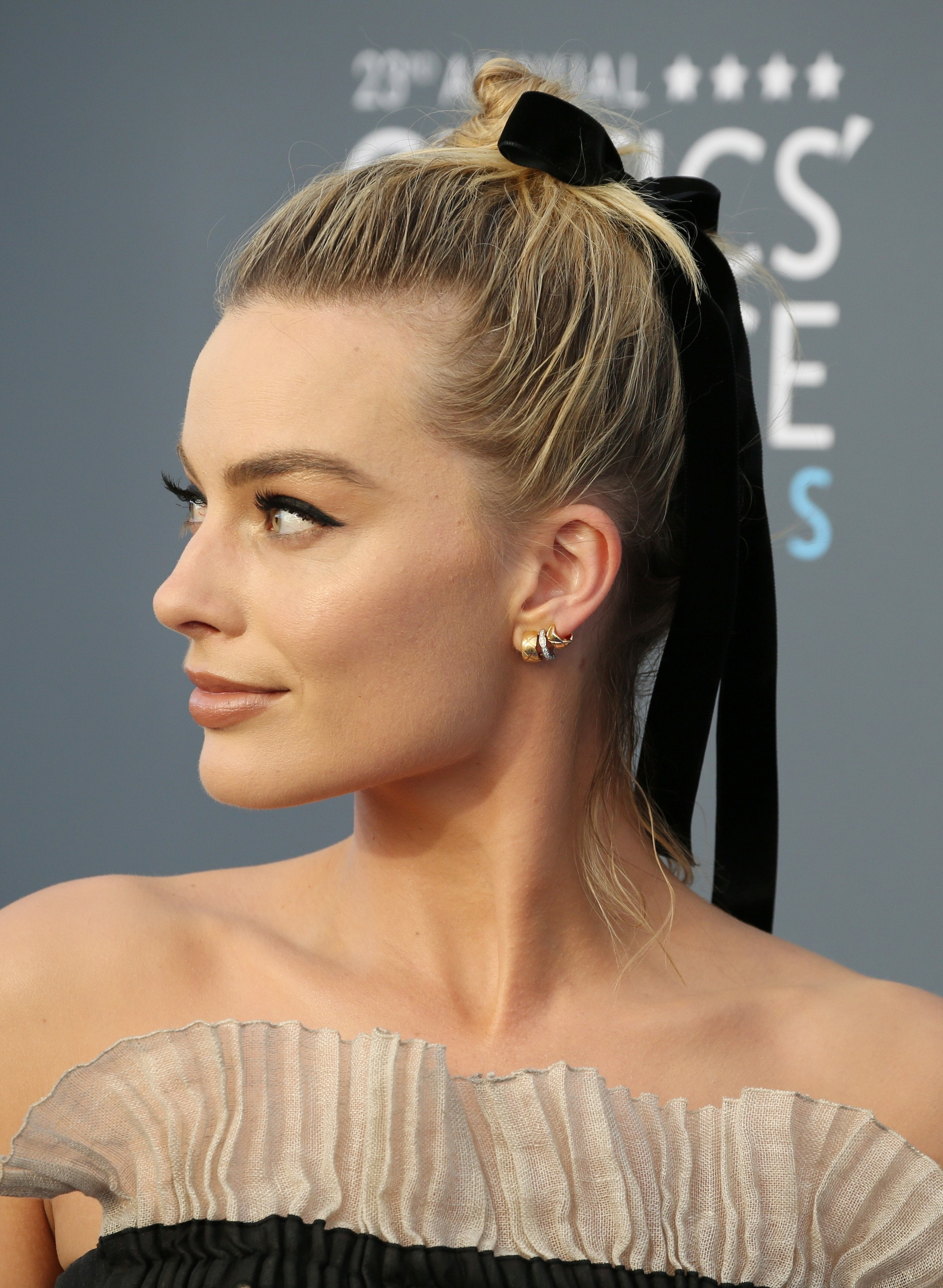 close up shot of margot robbie with topknot with ribbon tied around it, on the critics choice awards red carpet