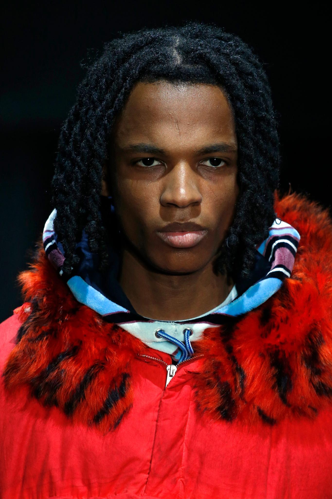 Milan Fashion Week Men's AW19: Male model with dark brown bob length hair twists, wearing a red coat