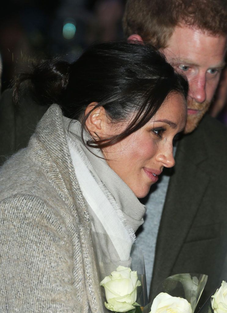 close up shot of meghan markle with low messy bun hairstyle, with loose tendrils at the front, standing next to prince harry on a recent outing