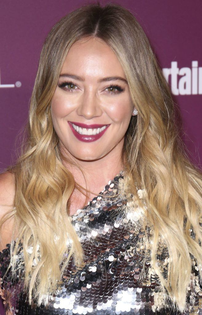 curly haircuts for round faces: close up shot of hilary duff with wavy long hair, smiling and wearing silver dress on the red carpet