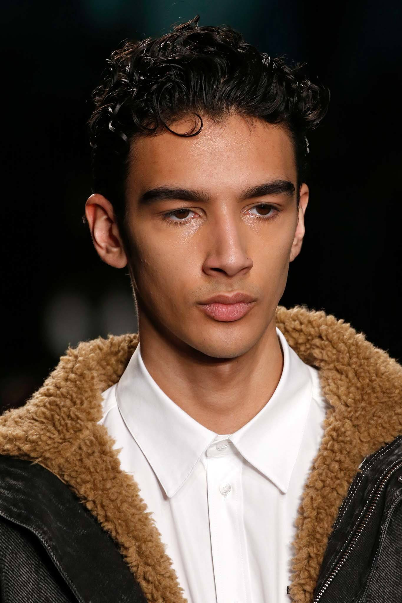 Milan Fashion Week Men's AW19: Runway shot of a male model with dark brown gelled curly hair, wearing a shearling jacket