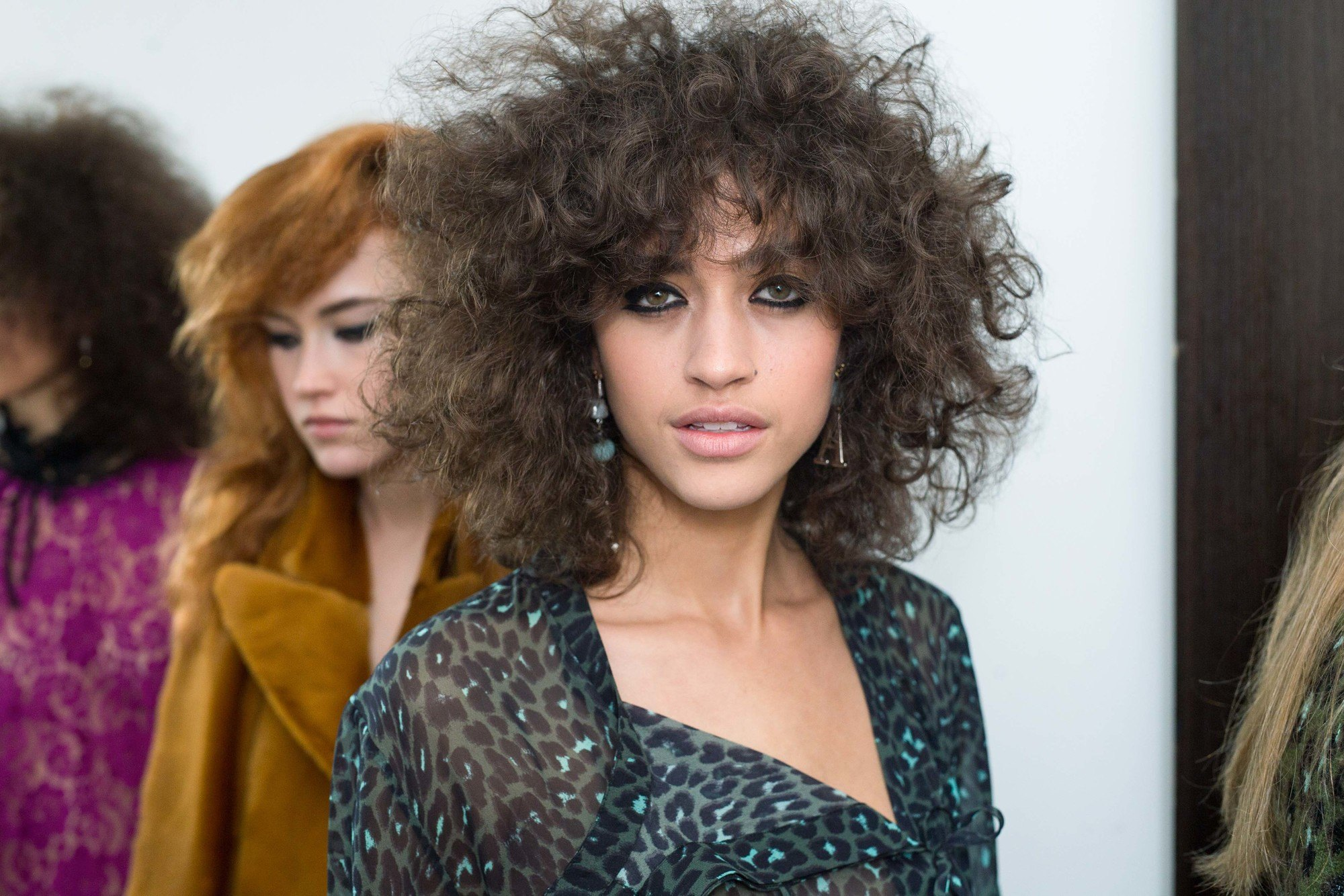Permed hair care tips woman with curly voluminous hair backstage at topshop show