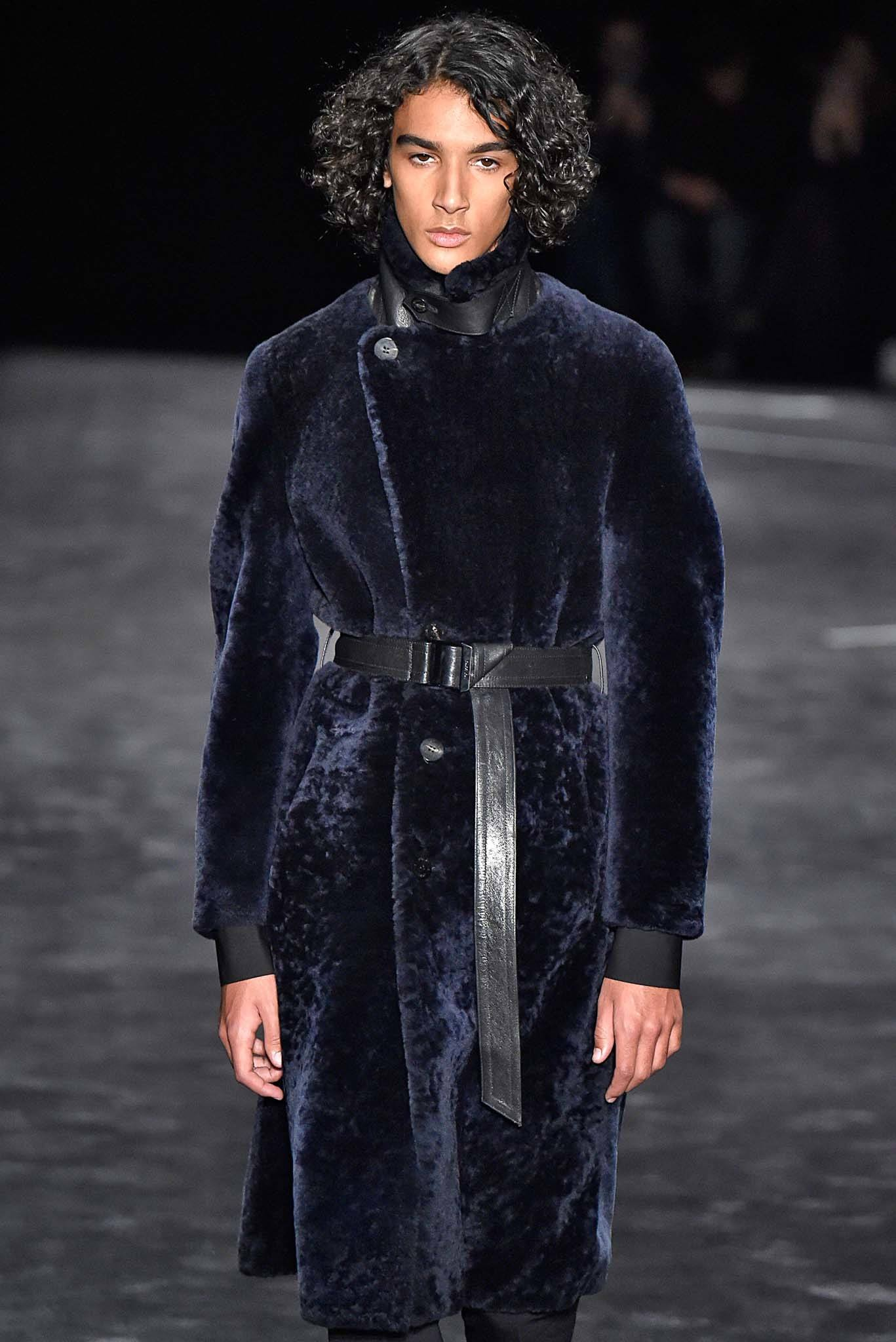 male model on catwalk with curly brown hair