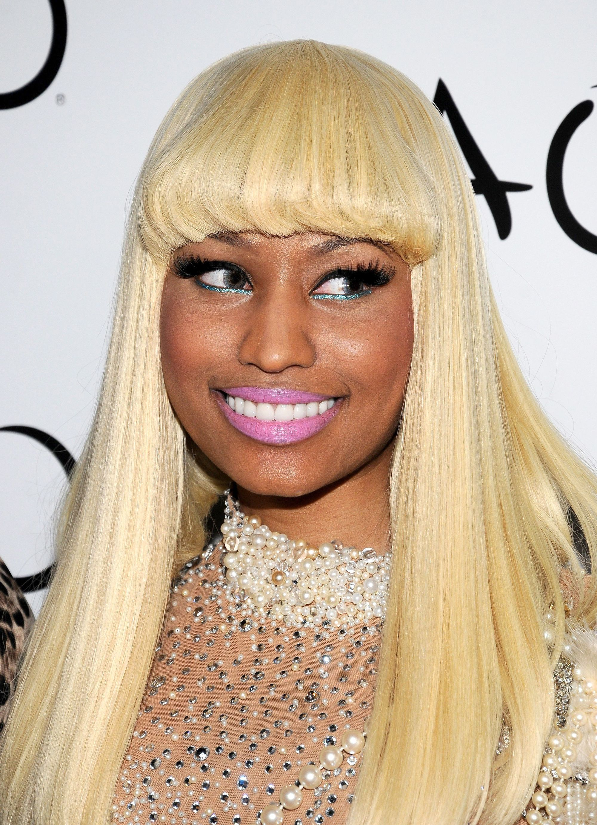 close up shot of nicki minaj with blonde hair, with heavy blunt fringe, posing on the red carpet