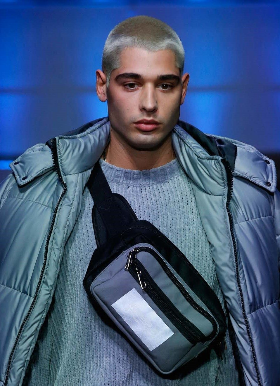 Milan Fashion Week Men's AW19: Male model on the runway with a blue tinted buzz cut, wearing a blue jumper and puffer jacket with a bumbag