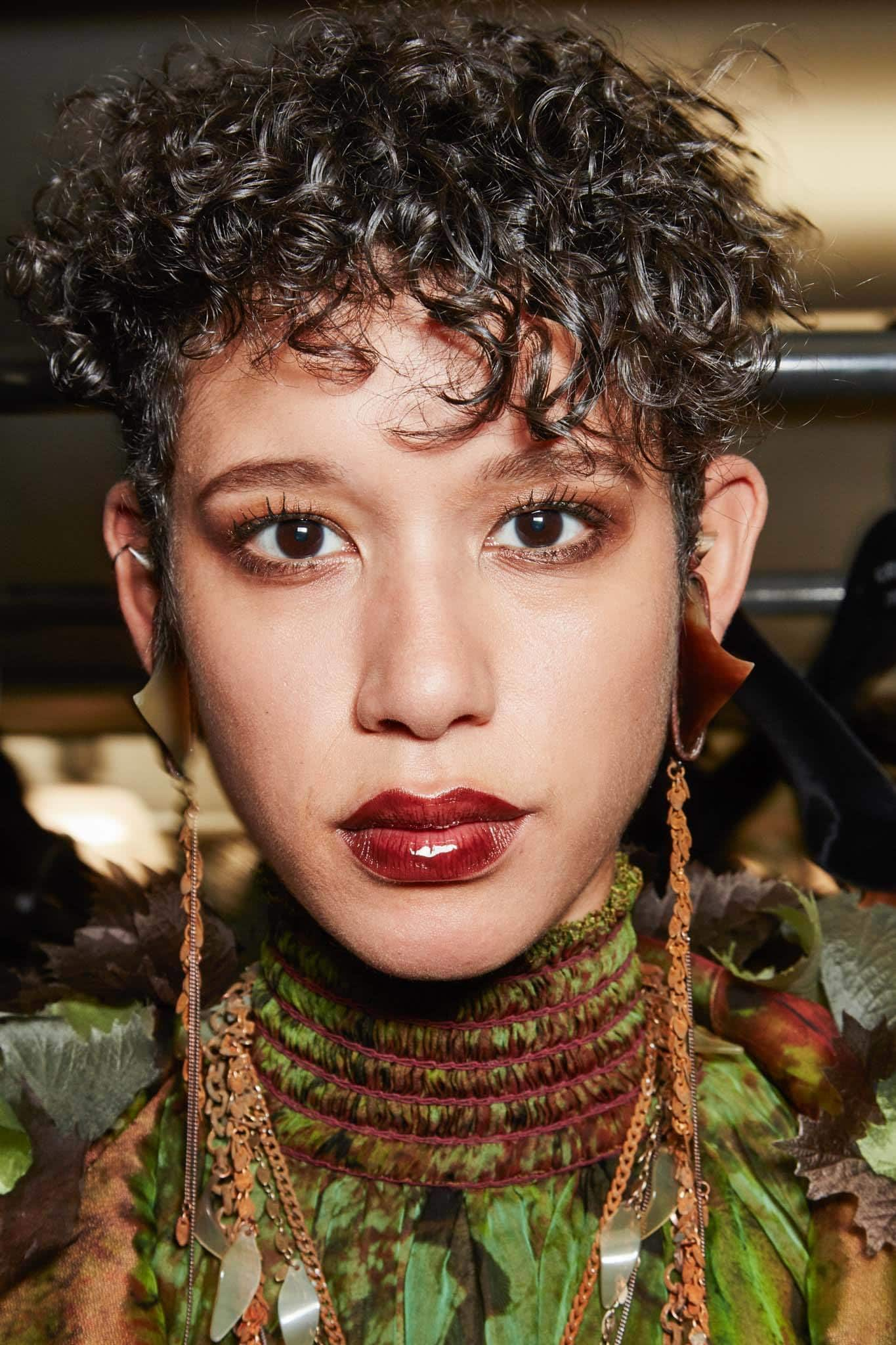 close up shot of woman with curly black pixie cut backstage at a show, wearing red lipstick and drop earrings