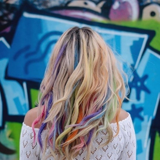back view of a blonde woman with rainbow hair chalk