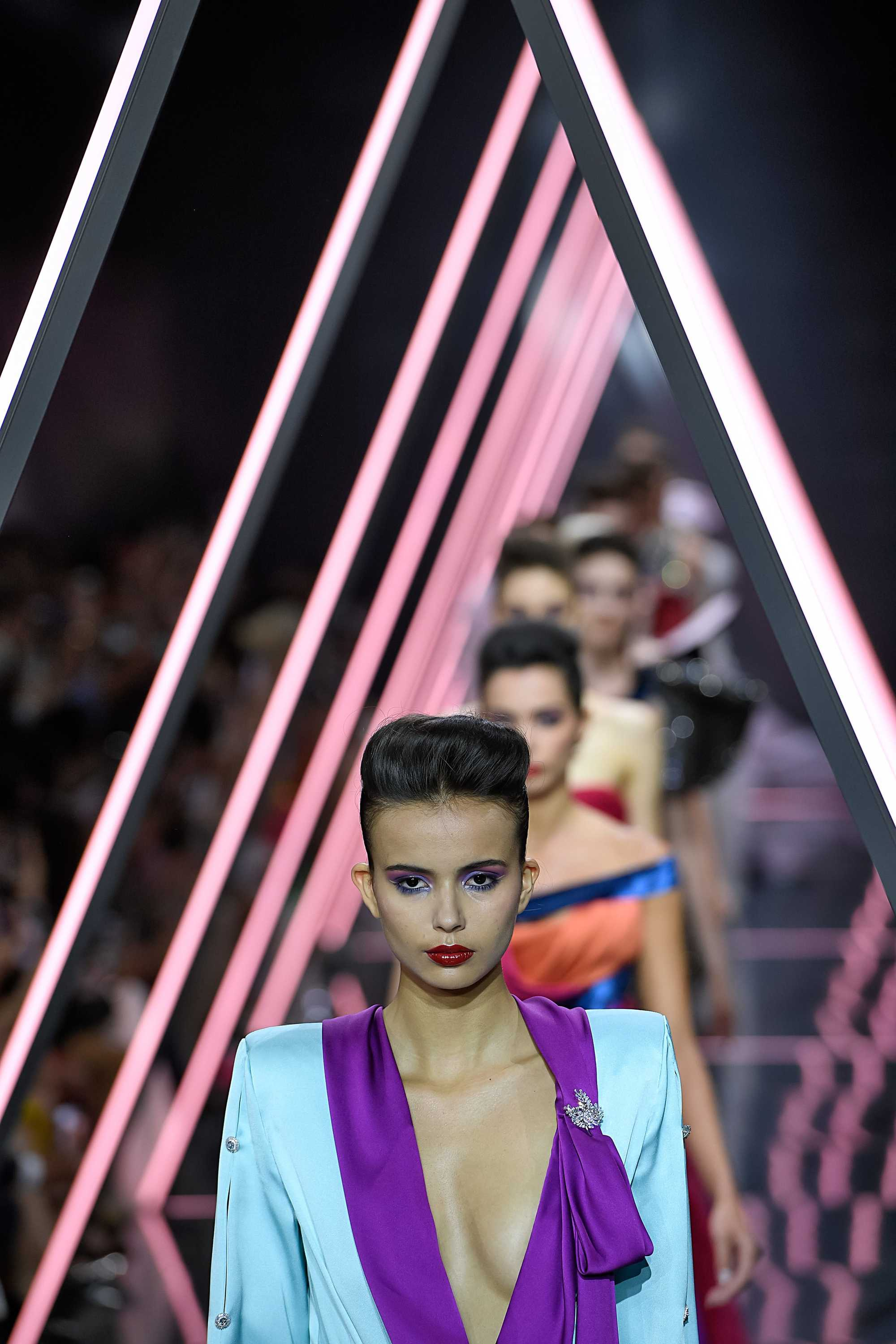 Paris Haute Couture Week fw18: close up shot a woman with short dark brown styled into a voluminous, swept-back quiff, wearing a colourful suit and walking down the ralph russo runway