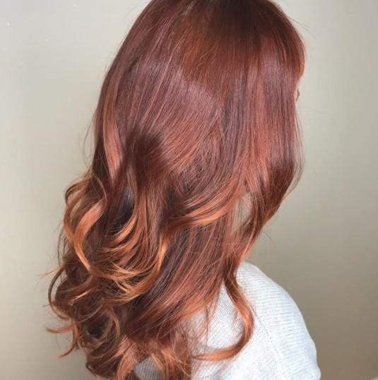 woman with long red copper ombre curly hair