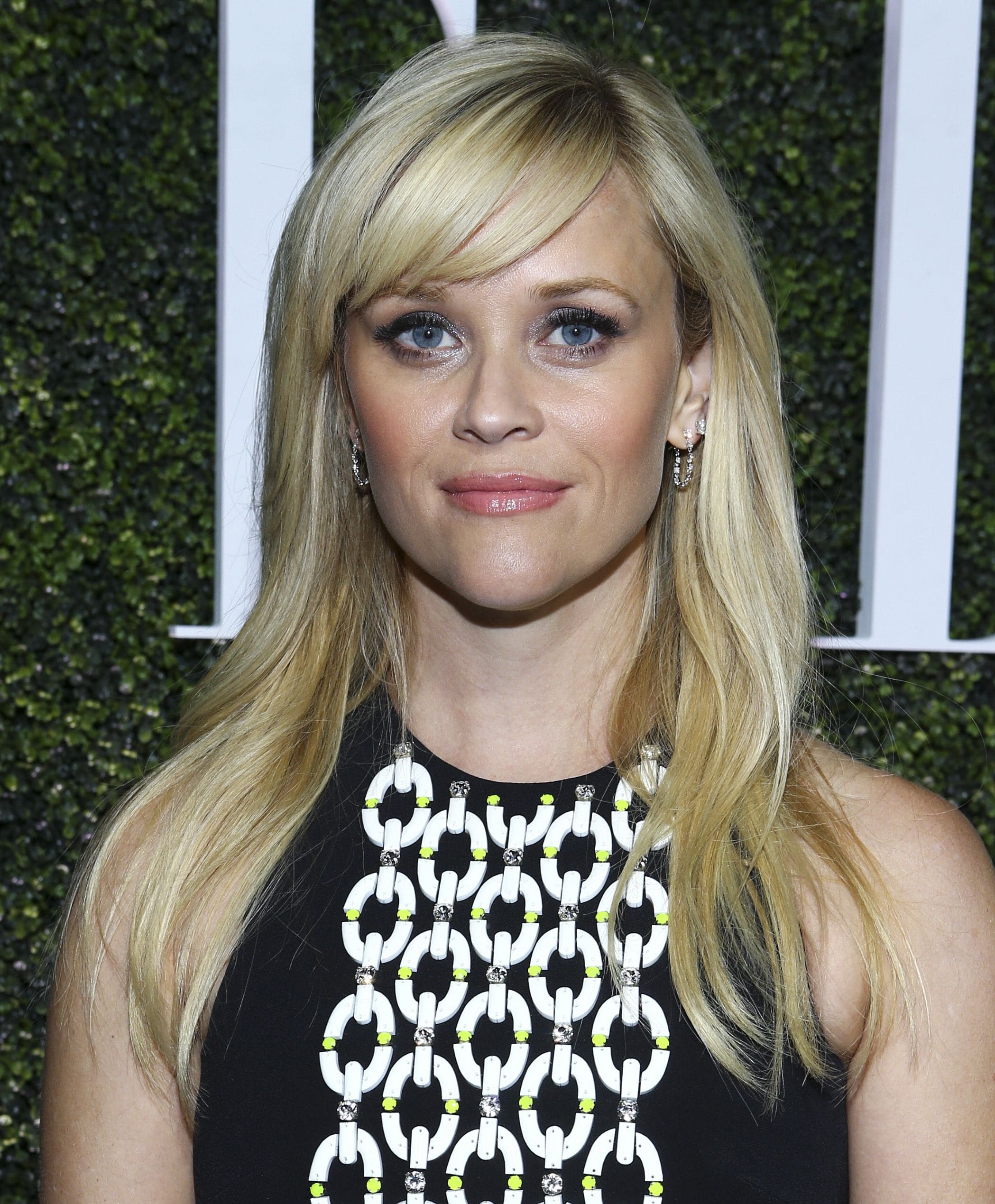 close up shot of reese witherspoon with sleek hairstyle with side fringe hairstyle, wearing all black top