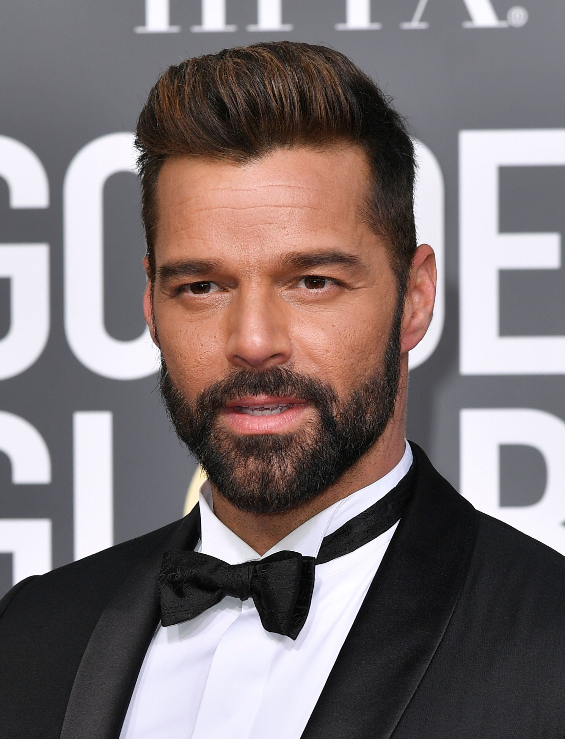 Golden Globes 2019: Close-up of Ricky Martin with brown hair in a quiff with facial hair, wearing a tux