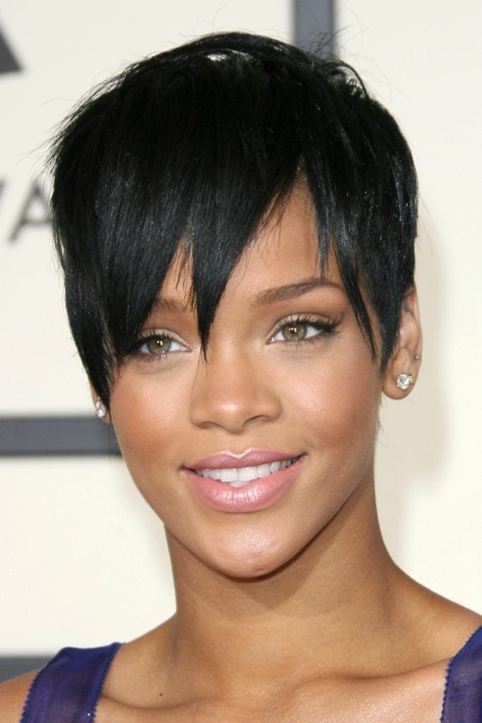 close up shot of rihanna with black pixie cut that has a side fringe, wearing blue dress on the grammy awards red carpet