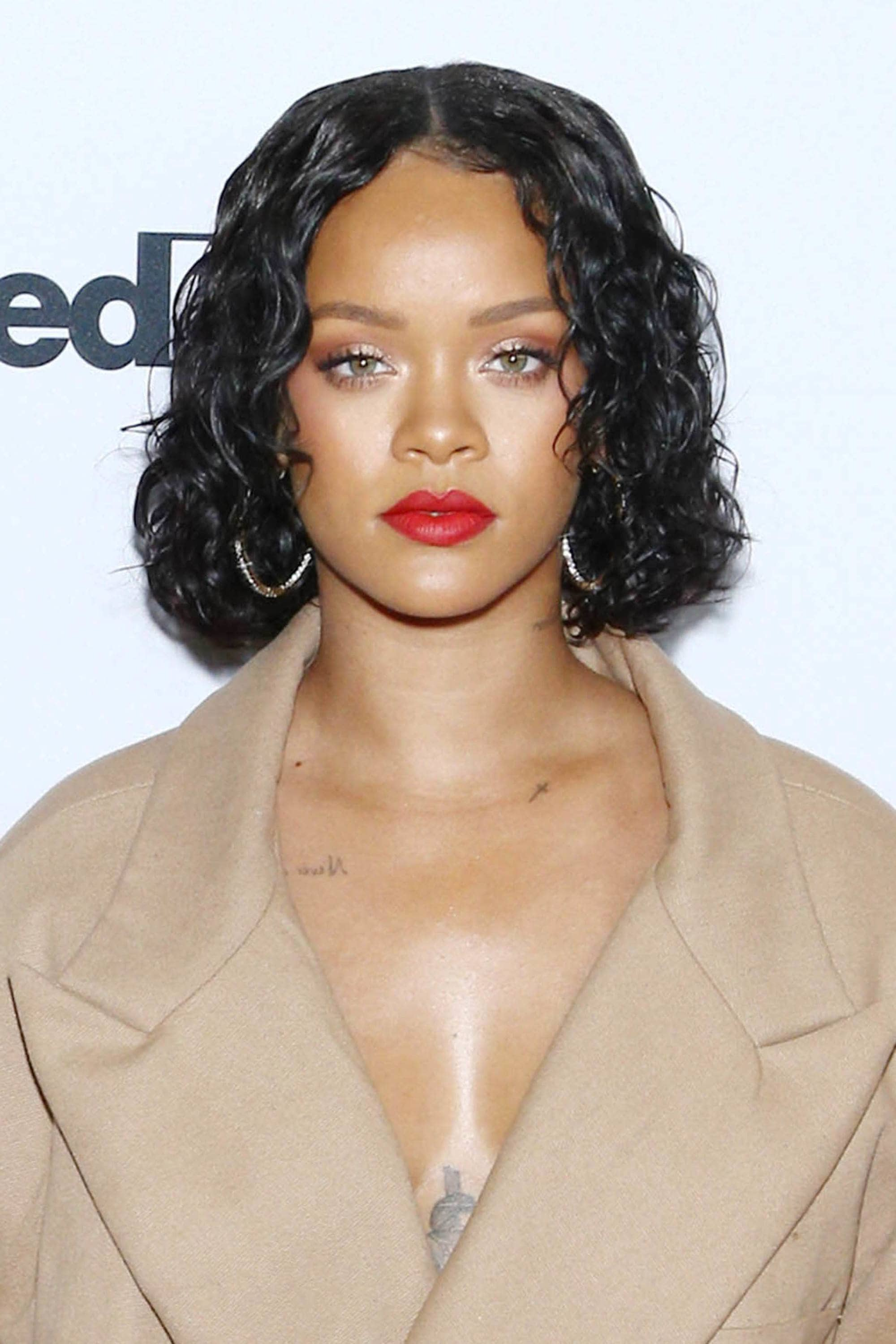 Rihanna on the red carpet with dark short curly bob hair, wearing red lipstick with camel jacket and hoop earrings