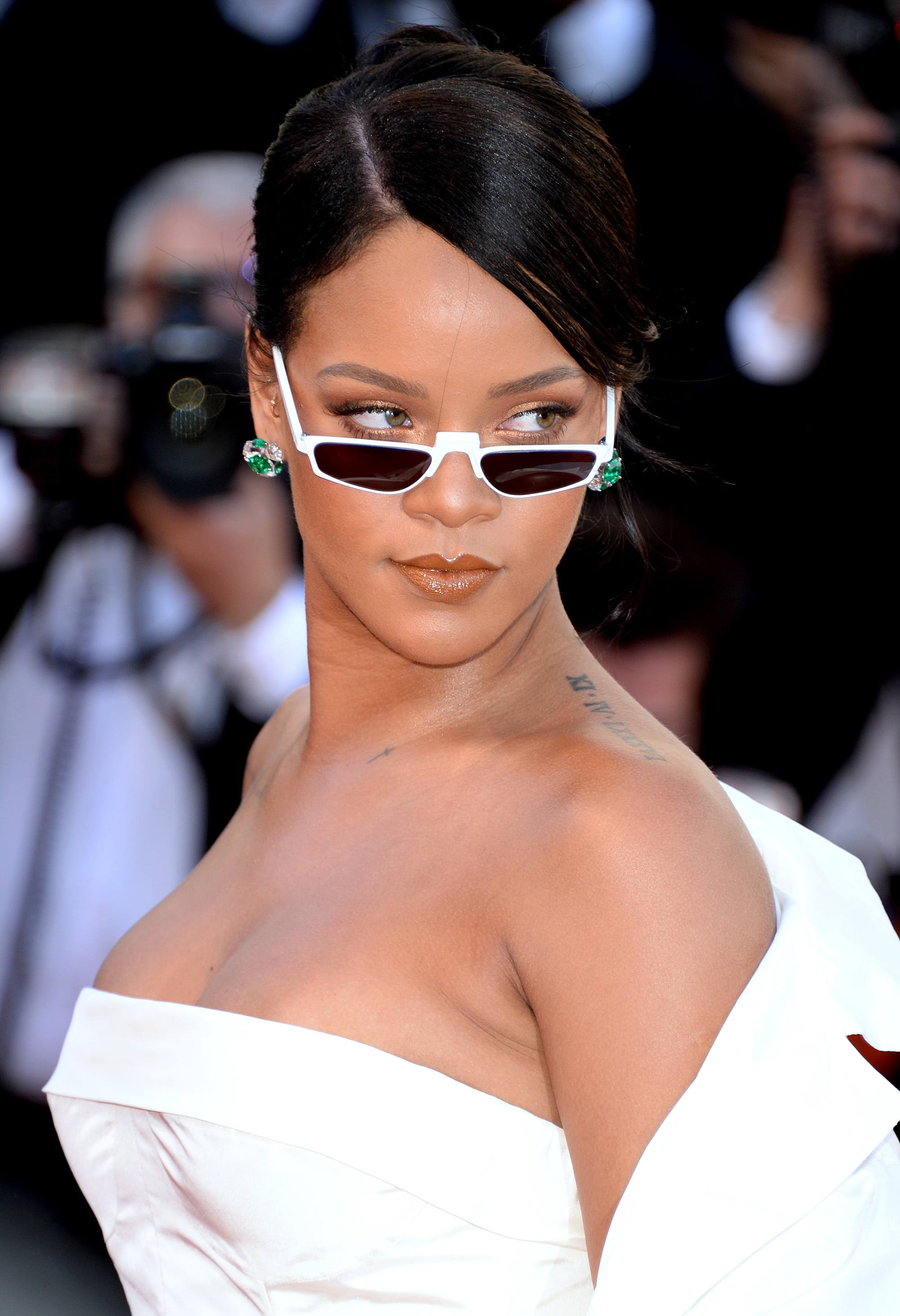 rihanna dark hair side part updo with micro sunglasses