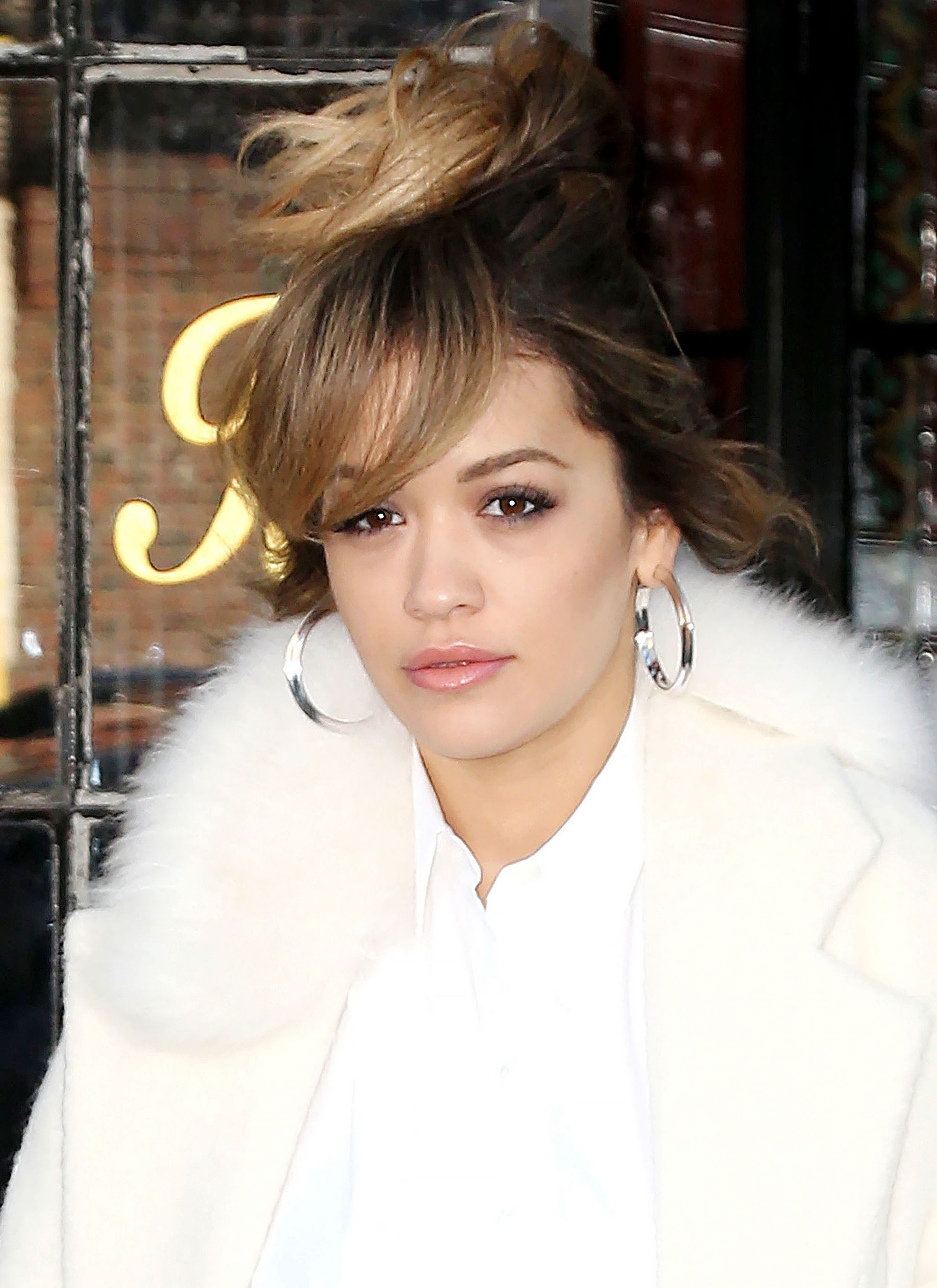 singer rita ora with sweeping side long bangs and a top knot