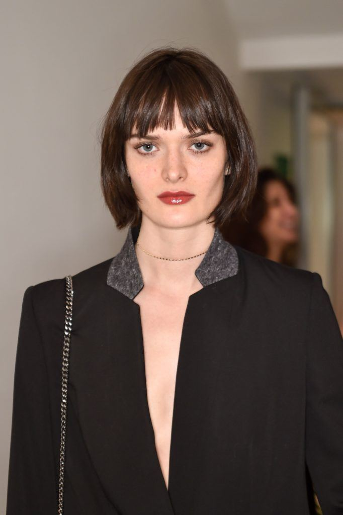 close up shot of sam rollins with sleek chanel haircut, wearing black jacket and posing at an event