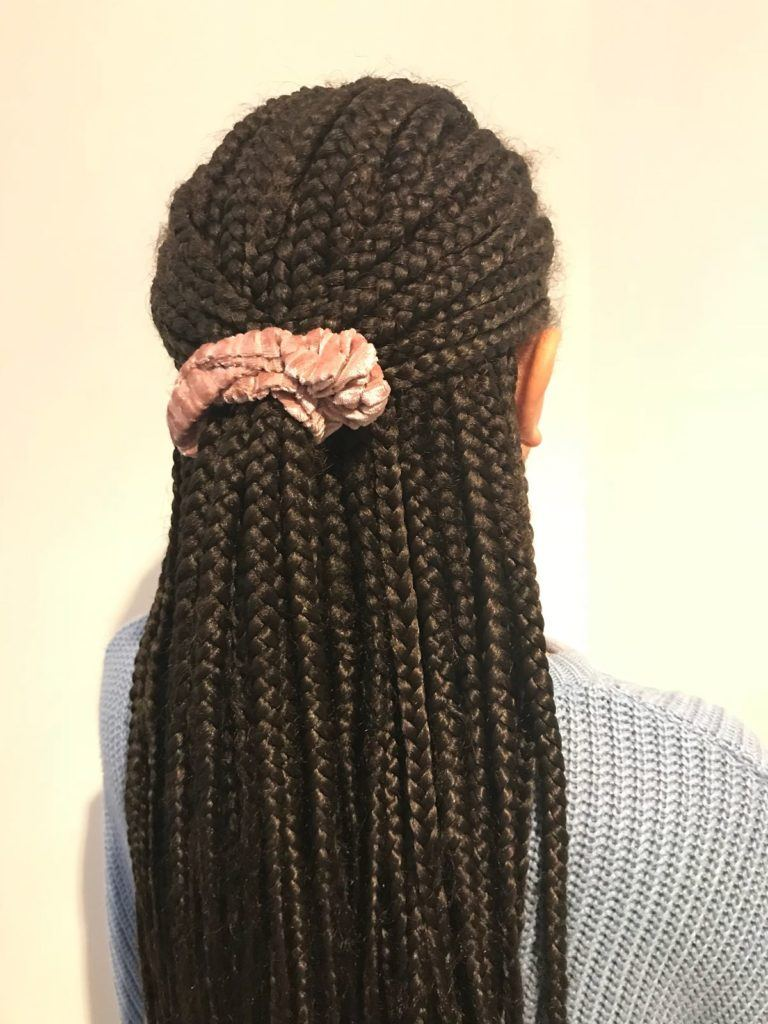 back shot of half up half down box braids styled into a half up style with a scrunchie