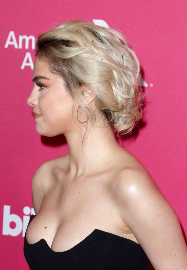close up shot of selena gomez with messy updo hairstyle, wearing low cut black dress on the red carpet