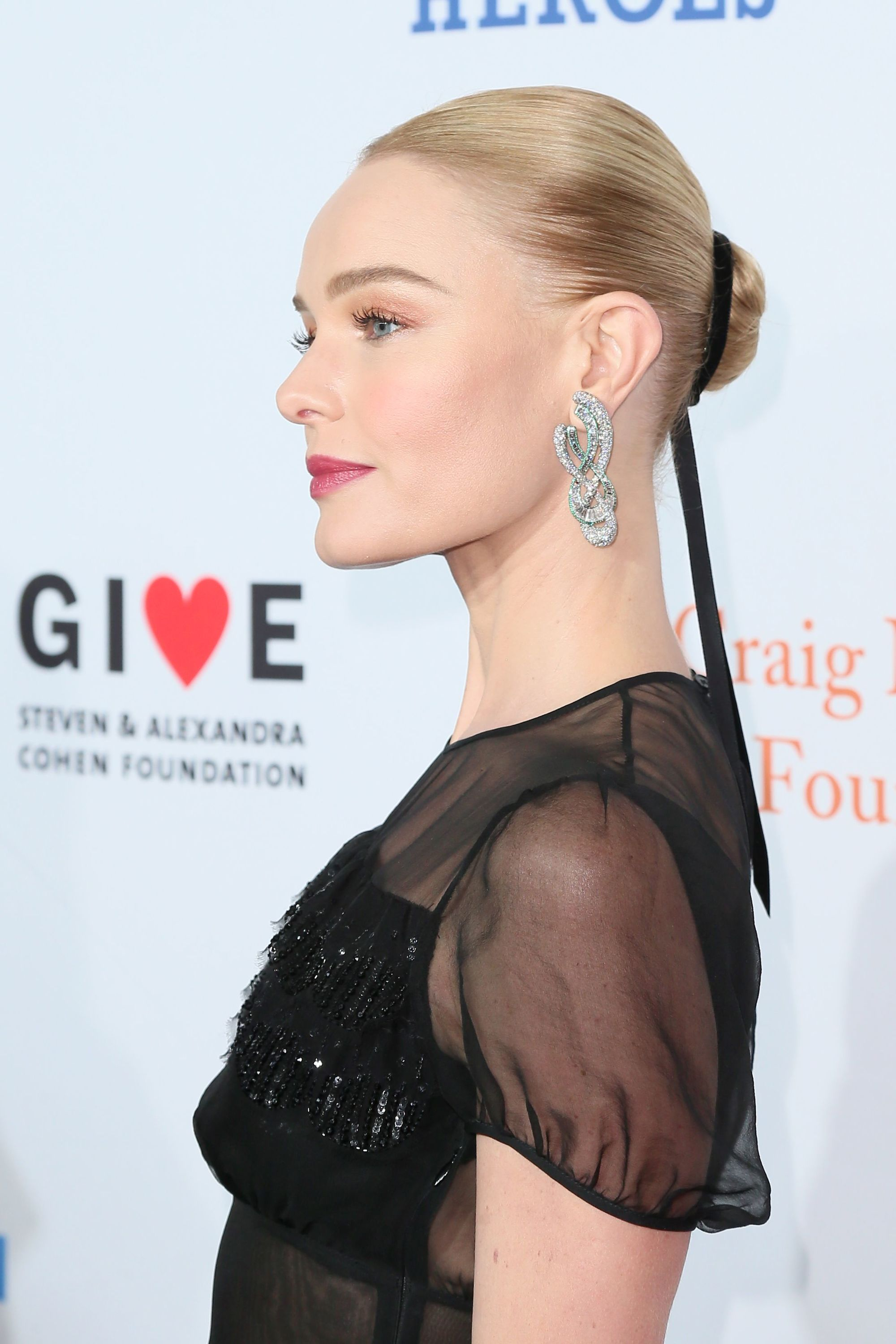 close up shot of kate bosworth with sleek short hair, wearing a ribbon hair accessory and posing on the red carpet