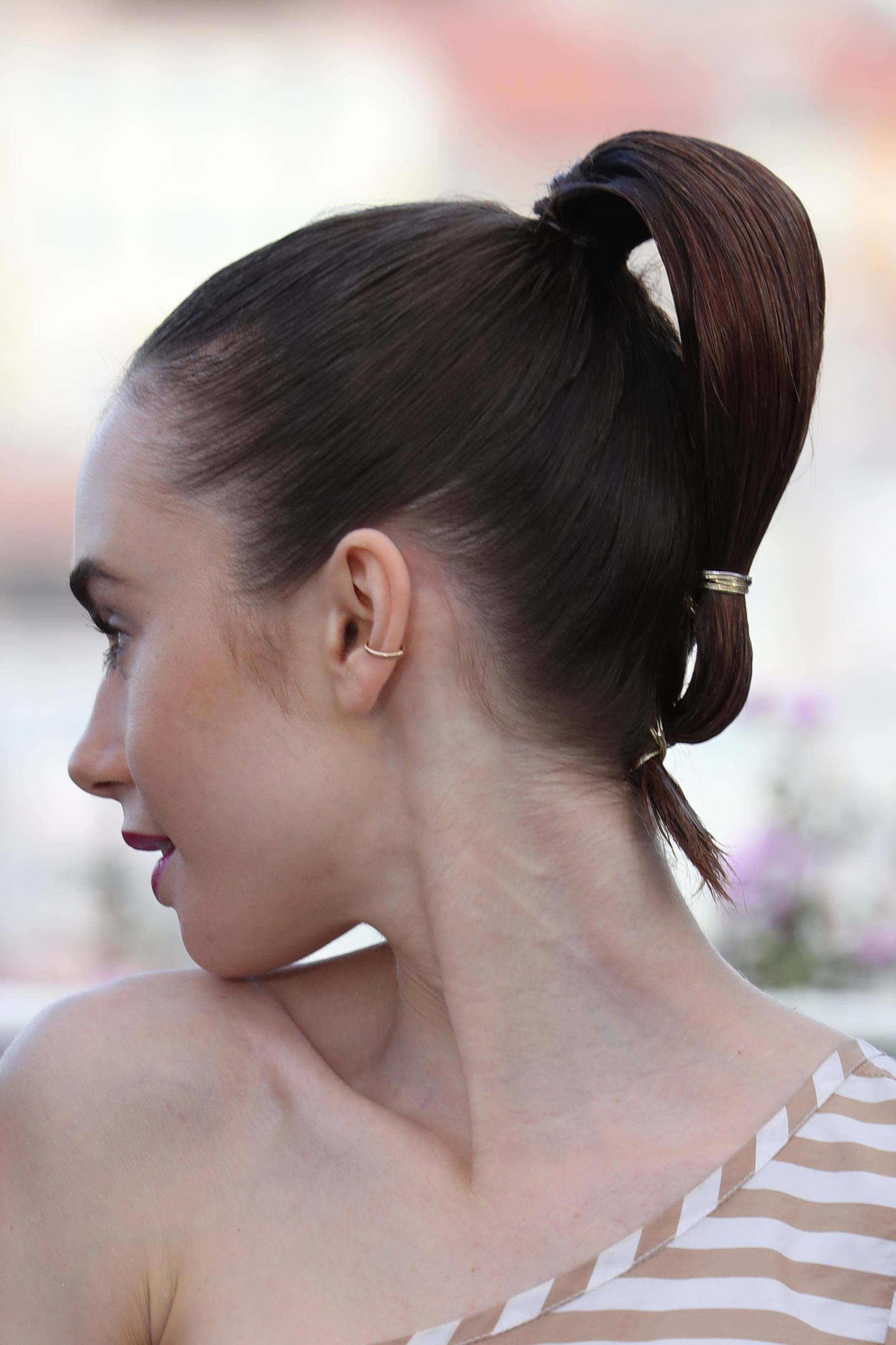 straight short hairstyles: close up shot of lily collins with sleek low looped ponytail, wearing all white on the red carpet and posing
