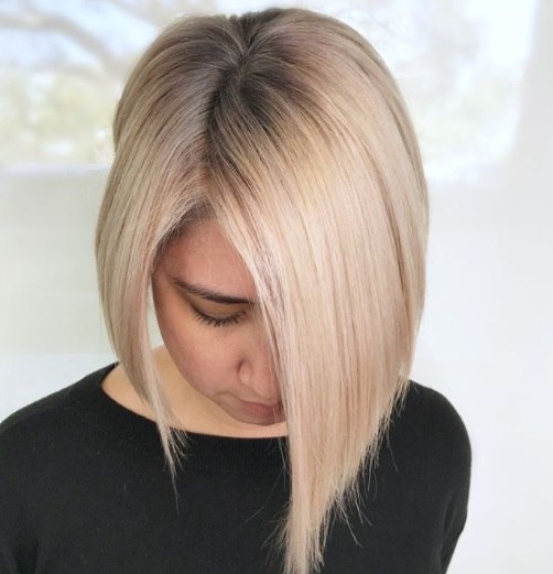 woman with a line ash blonde hair with dark shadow roots