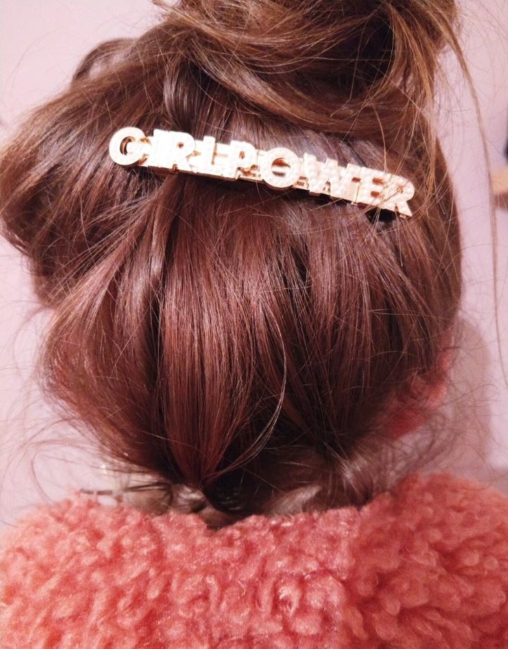 Hair trends 2019: Brown straight hair in high messy bun with statement girlpower barrette hair slide.
