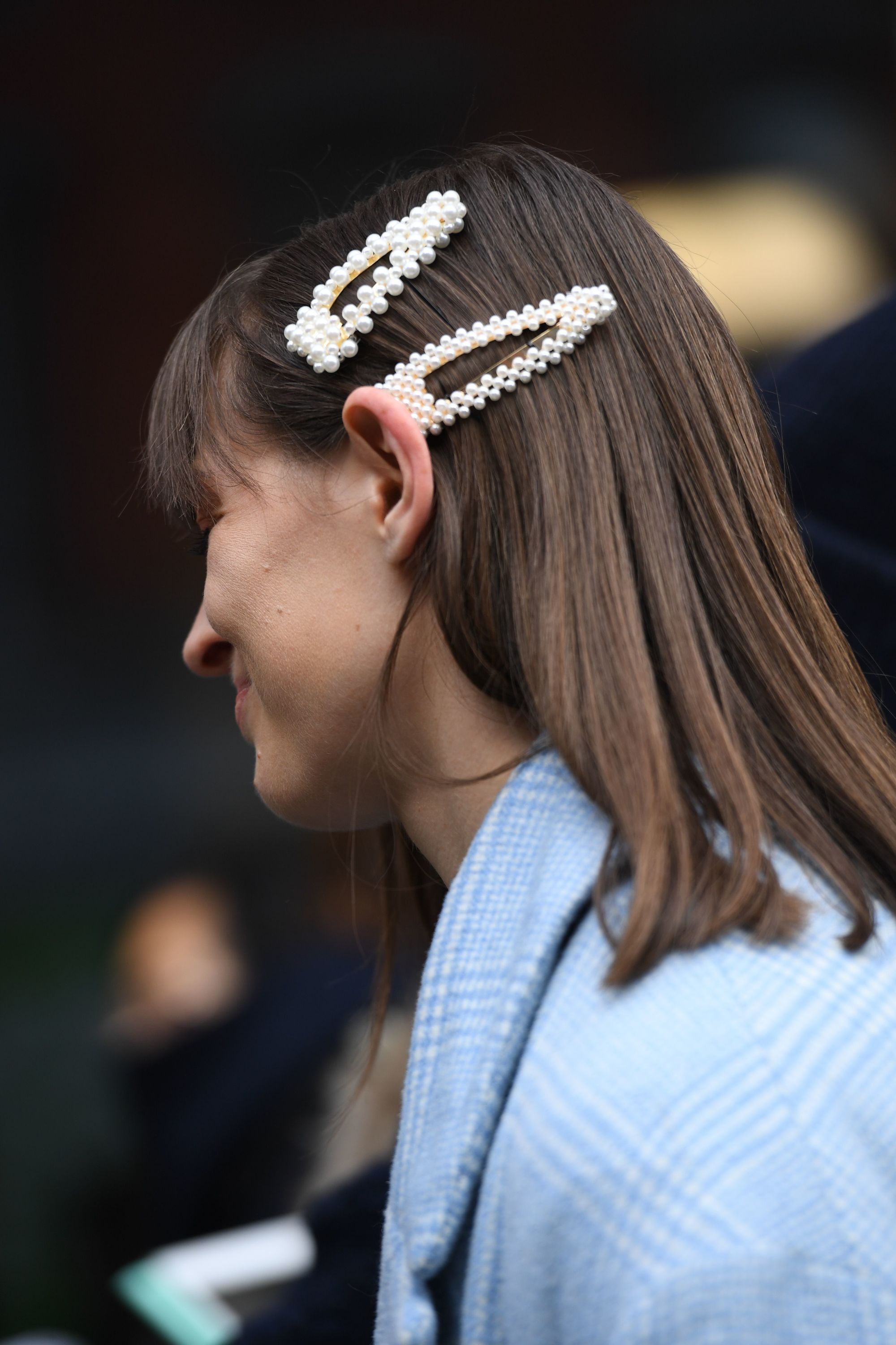 Hair trends 2019: Street style woman with shoulder length straight brown hair with bangs styled with pearl hair clips wearing a baby blue jacket.