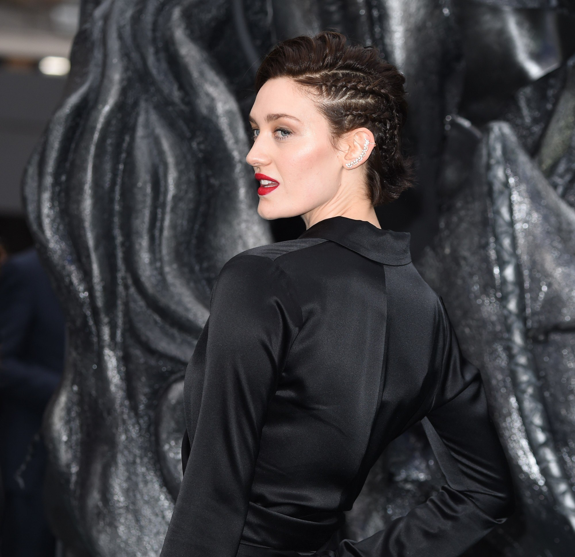 close up shot of tess haubirch with long pixie hairstyle with side braids in it, wearing all black on the red carpet
