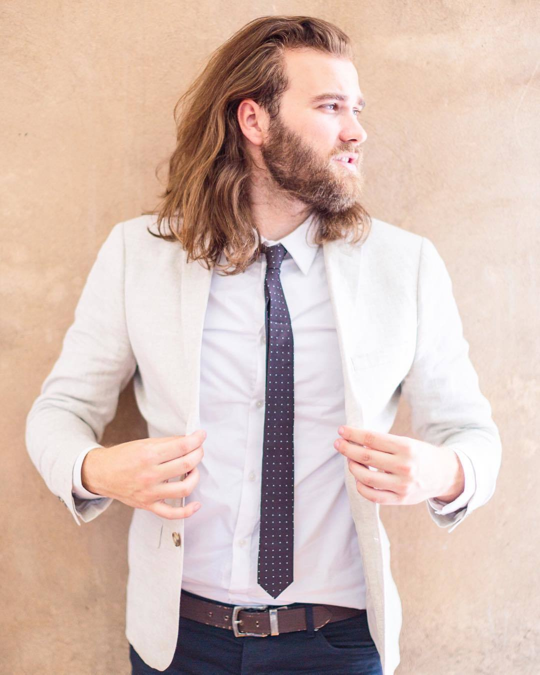 Viking Hairstyles: Man with rugged beard with shoulder length light brown wavy hair, wearing white top with black tie and white suit jacket outside