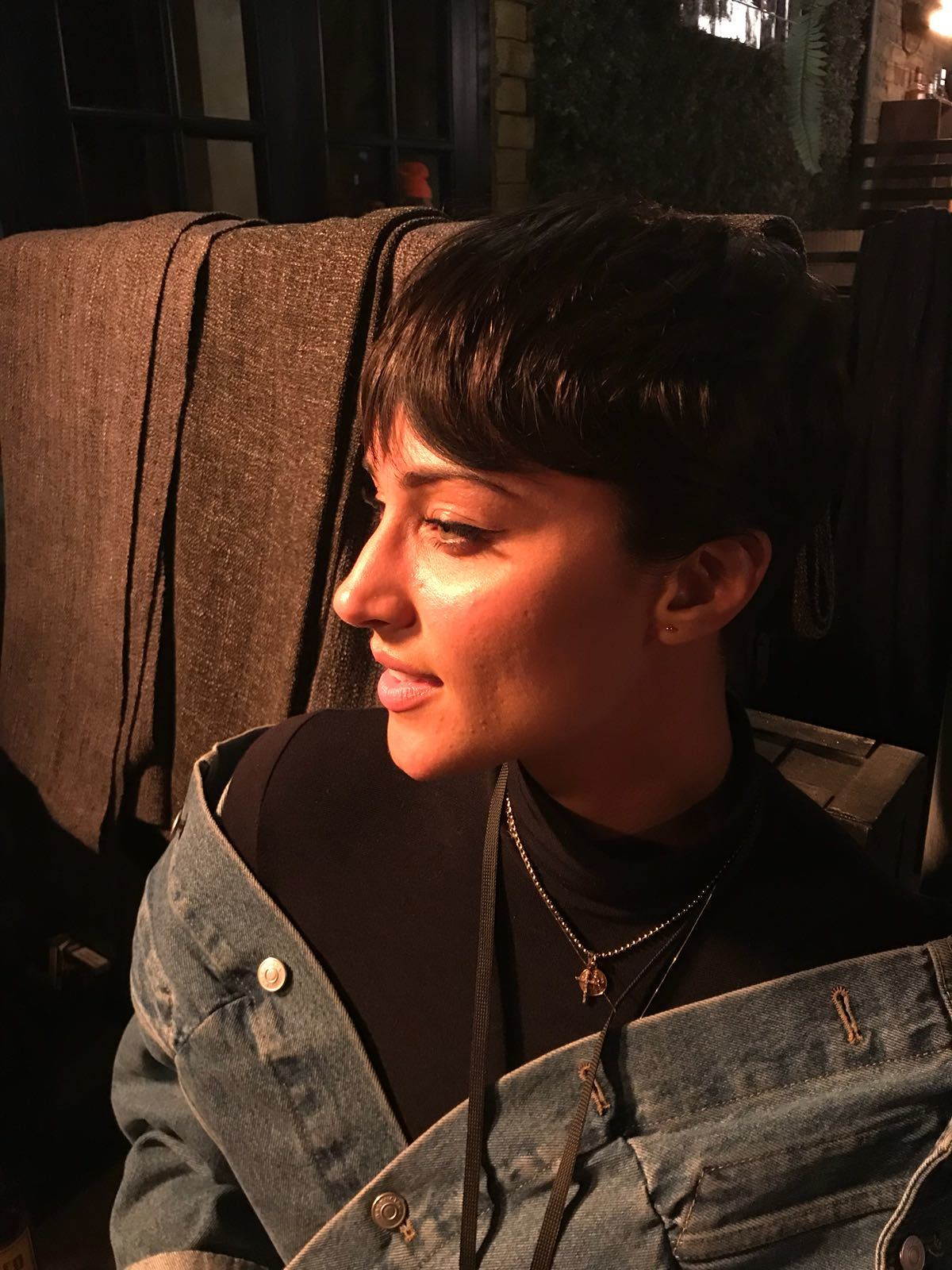 close up shot of tia ward with tousled pixie haircut, wearing blue denim jacket and posing at the nme and vo5 awards event