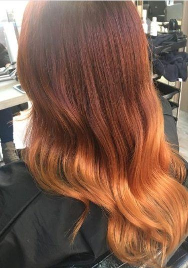 back view of a woman with glossy copper ombre hair