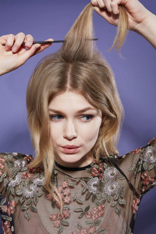 Beehive hair blonde girl backcombing roots with brush looking down