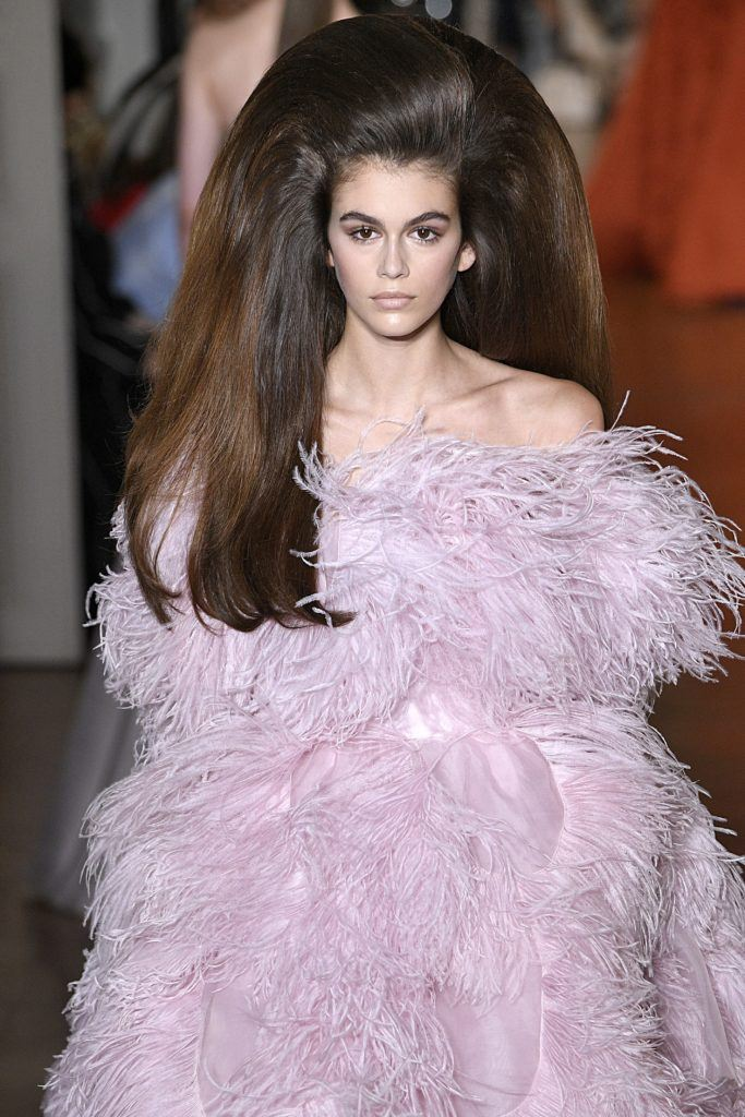 Paris Haute Couture Week fw18: close up shot of a model on the runway with chocolate brown hair styled into a glamorous bouffant, wearing a feathery purple dress and walking down the Valentino runway