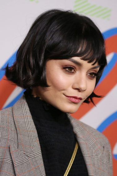 close up shot of vanessa hudgens with chanel haircut, wearing blazer and dark top and posing on the red carpet