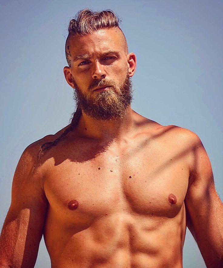 Viking Hairstyles: Man with swept back hair styled into skinny braid, with rugged beard on the beach