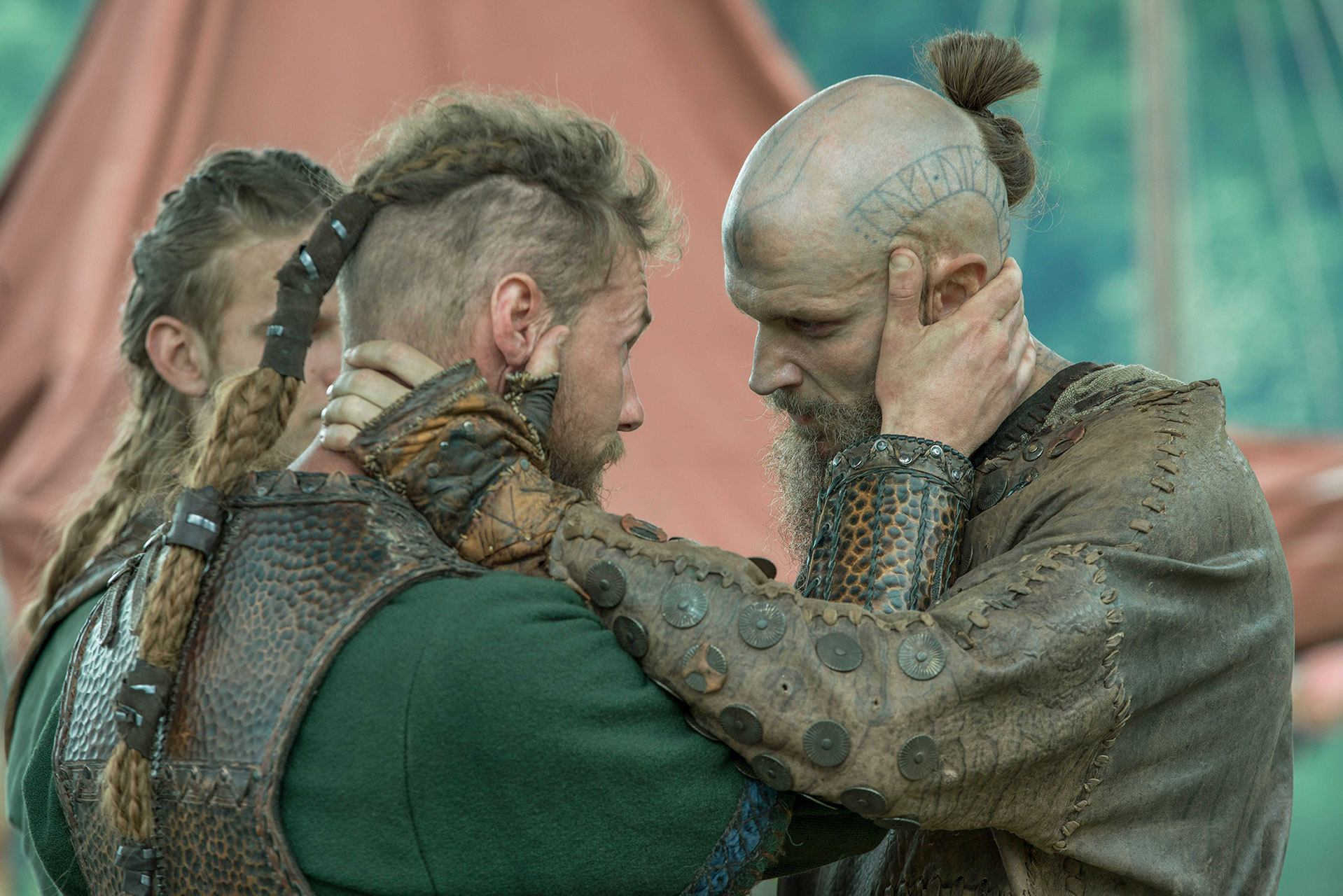 Viking Hairstyles: Ragnor with long braided ponytail, holding fellow actor in film still